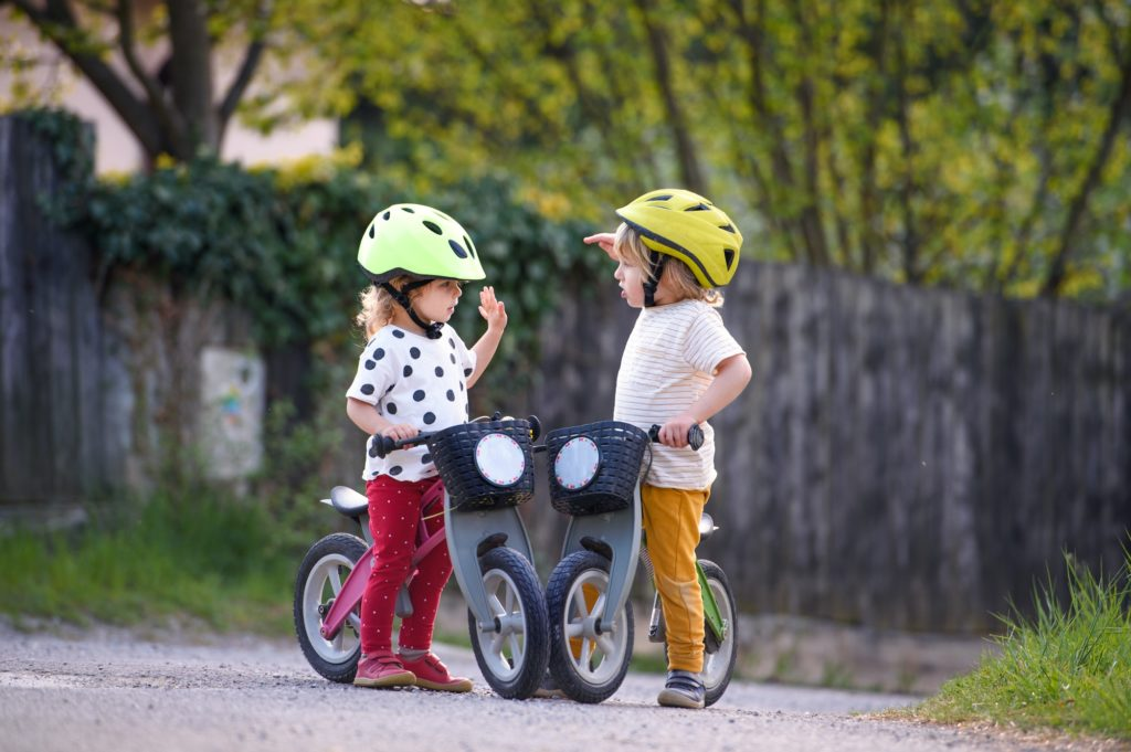 Small children boy and girl with helmets and balance bikes outdoors playing