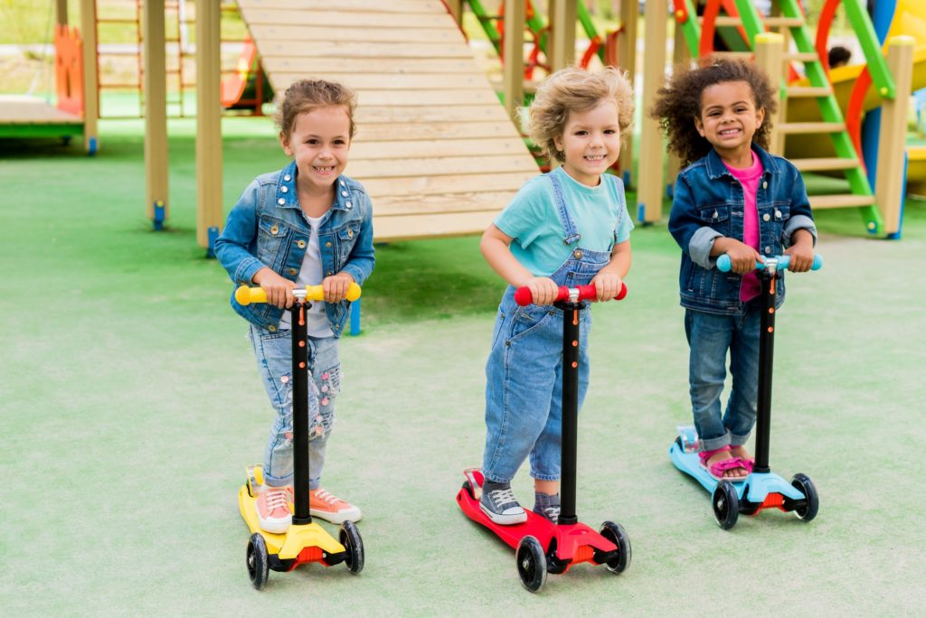 three multicultural adorable little children riding on kick scooters at playground
